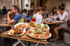 Oidentifierat folk som äter traditionell italiensk mat i utomhus- restaurang fotografering för bildbyråer