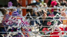 Oidentifierat folk som binder dålig förmögenhet som berättar remsan, Omikuji på den Sensoji templet, Asakusa, Tokyo, Japan royaltyfri fotografi