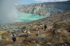 Oidentifierat folk som bryter svavel från den aktiva vulkan av Mt Royaltyfri Bild