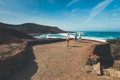 Oidentifierat folk som går i El Golfo och grön lagun Golfen är en lagun i ett vulkaniskt c arkivfoto