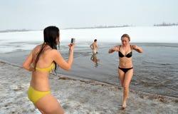 Oidentifierat folk som simmar i kallt vatten under Epiphany Arkivfoto