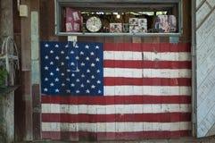 Oidentifierat shoppa är målarfärg väggen framme av lagret som en flagga av Amerika Arkivfoto