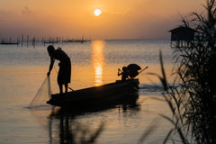 The oider boy are fishing at sunset. Royalty Free Stock Photos