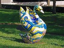 Oie en céramique décorative Artsy se reposant dans une pelouse d'herbe verte image stock