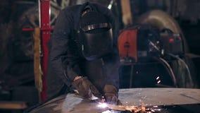 Oigenkännlig arbetare som utrustas all med det skyddande klädersnittstycket av mettal med en industriell bitande fackla stock video