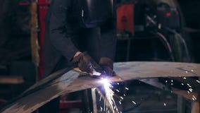 Oigenkännlig arbetare som utrustas all med det skyddande klädersnittstycket av mettal med industriellt använda för bitande fackla lager videofilmer