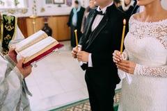 Oigenkännlig brud och brudgum i kyrkan under den kristna bröllopceremonin Händer av en präst med bibeln Arkivbilder