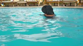 Oigenkännlig Caucasian hög äldre kvinna i bad för svart hatt i pöl för blått vatten i hotell Mot bakgrunden av lager videofilmer