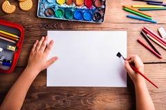 Oigenkännlig flickamålning på det tomma arket av papper fotografering för bildbyråer