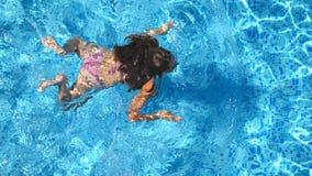 Oigenkännlig härlig flicka som svävar över pölen av hotellet Simning för ung kvinna i klart blått vatten av handfatet på stock video