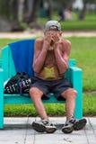 Oigenkännlig hemlös i Miami Beach sammanträde på en bänk Arkivfoto
