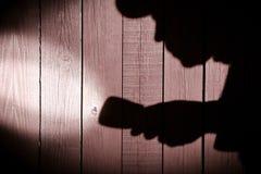 Oigenkännlig inbrottstjuv med ficklampan i skugga på wood backg arkivfoton