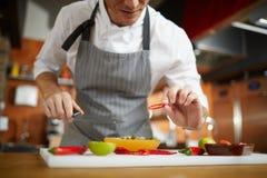 Oigenkännlig kock Cutting Vegetables royaltyfria foton