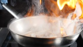 Oigenkännlig kock som kastar den varma icke-pinne stekpannan med skaldjur, då ställer den in på brand som lagar mat flambematrätt lager videofilmer
