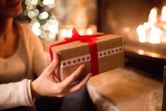 Oigenkännlig kvinna framme av julgranen som ger gåva arkivbilder
