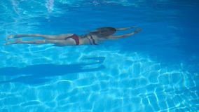 Oigenk?nnlig kvinna i baddr?ktsimning under vatten i p?l med kristallklart vatten Ung flicka som kopplar av under arkivfilmer