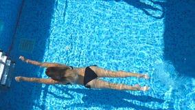 Oigenkännlig kvinna, i svart simma för bikini som är undervattens-, och att dyka upp på yttersida Sexig flicka som kopplar av und lager videofilmer