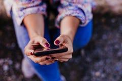 Oigenkännlig kvinna på solnedgången genom att använda mobiltelefonen Livsstil och teknologibegrepp arkivfoto