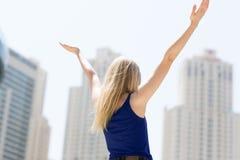 Oigenkännlig kvinna som förbiser staden med hennes armar upp i luften isolerad white för beröm begrepp royaltyfri foto