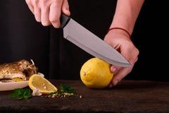 Oigenkännlig kvinna som klipper den nya citronen på träbrädet för maträtten i köket, sikt av handnärbilden på svart bakgrund Arkivfoto