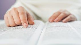 Oigenkännlig kvinna som läser den stora boken - helig bibel och be Kristen studerande scripture Student i högskolan fotografering för bildbyråer