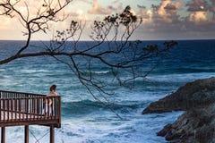 Oigenkännlig kvinna som ser havet från terrass royaltyfria bilder