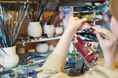 Oigenkännlig kvinnlig konstnär Making Glass Sphere Royaltyfri Bild