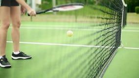 Oigenkännlig kvinnlig som studsar en tennisboll inom domstolen lager videofilmer
