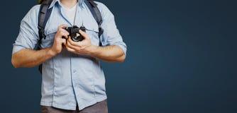 Oigenkännlig man för manhandelsresandeBlogger med ryggsäck- och filmkameran på blå bakgrund Fotvandra turismresabegrepp royaltyfri fotografi