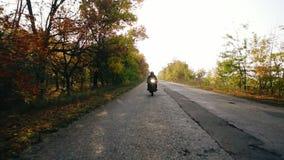 Oigenkännlig man i det svarta hjälm- och läderomslaget som att närma sig, medan rida en motorcykel på en väg på en solig dag in stock video