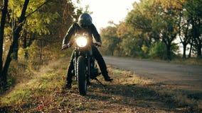 Oigenkännlig man i hjälm- och läderomslaget som upp till kommer hans cykel och start motorn, medan stå på arkivfilmer