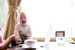 Oigenkännlig man i kafét som har kaffe som rymmer hans son Arkivfoton