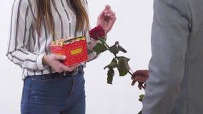 Oigenkännlig man och kvinna på ett datum, man att ge den närvarande och röda rosen för kvinna Isolerade unga par för nära övre st