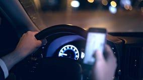 Oigenkännlig man som kör bilen på natten och rengöringsduken som surfar telefonfarabegrepp lager videofilmer