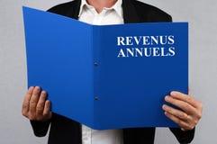 Oigenkännlig man som läser årsinkomstmappen som är skriftlig i franskt royaltyfria foton