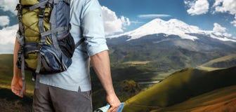 Oigenkännlig manlig handelsresande med en ryggsäck som ser in i avståndsbergen, bakre sikt Affärsföretagdestinationsbegrepp royaltyfri foto