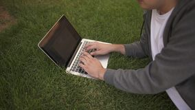 Oigenkännlig manmaskinskrivning på hans bärbar dator som ligger på en gräsmatta, sidosikt arkivfilmer