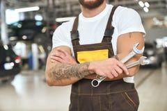 Oigenkännlig mekaniker i overaller som rymmer skiftnycklar arkivbild