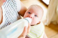Oigenkännlig modermatning behandla som ett barn sonen, mjölkar i flaskan, slut upp Arkivbild