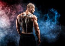 Oigenkännlig muskulös man med tatueringen på baksida mot av svart bakgrund isolerat arkivbilder