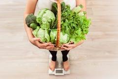 Oigenkännlig slank flicka som kontrollerar vikt på den hållande korgen för skala av nya grönsaker och grönt kött Arkivfoto