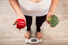 Oigenkännlig slank kvinna som kontrollerar vikt på skala och hållande grönsaker Fotografering för Bildbyråer