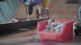 Oigenkännlig snickare som gör korridorer i träflismaterialdetaljerna med sladdlös skruvmejsel Begrepp av handtillverkning lager videofilmer