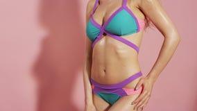 Oigenkännlig stående av den unga kvinnan som poserar i bikini över rosa bakgrund stock video