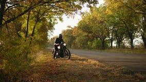 Oigenkännlig stilfull man i hjälm- och läderomslaget som upp till kommer hans cykel och start motorn, medan stå på lager videofilmer