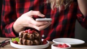 Oigenkännlig tonårs- flicka som spiller kaffe, medan genom att använda en mobiltelefon stock video