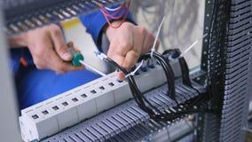Oigenkännlig yrkesmässig elektriker som monterar den elektriska skölden arkivfilmer