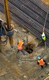 Oigenkännliga arbetare med den hydrauliska hammareborrandemaskinen på Arkivfoton