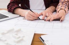 Oigenkännliga arkitekter som diskuterar bygga plan Royaltyfria Foton