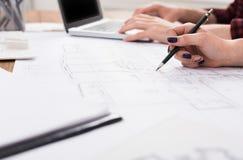 Oigenkännliga arkitekter som diskuterar bygga plan Arkivfoto